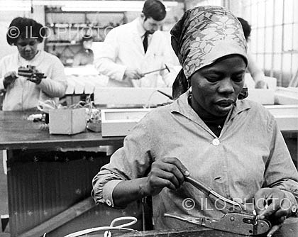 Juliana Bankole, a skilled Nigerian worker, at work in a north London suburb. At the time, half the company's staff were women and one quarter were immigrants. Management in no way discriminated on the grounds of sex or race. Through its conventions, ILO seeks to make such working conditions the rule. Undated.