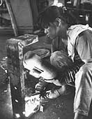 Young woman welder working in a tool factory.