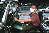 'Tuk-tuk' driver in Bangkok wearing an anti-pollution mask.