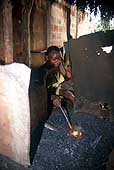 Benin 2001, Bohicon. Child working as blacksmith moves a bellows.