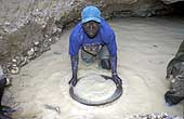 Benin 2001, Perma gold mine. Child panning for gold in a hole dug on the banks of a river.