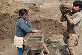 Huachipa, children fill the moulds for making bricks