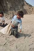 Huachipa, child covering the bricks with sand in order to dry them