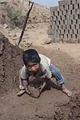 Huachipa, child gathering mud for bricks