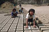 Huachipa, children turn bricks over for drying