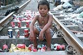 Child recycling beverage cans in a shantytown of Manila