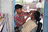 Rambabu, 13 years old, has been working for two years as a hair dresser in his father's hair salon in the heart of Vasant Vihar (New Delhi)'s shanty town.