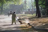 6 o'clock in the morning, domestic worker sweeping the street in front of a private property in the Golf Links area, Delhi.