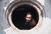 Prakash, sewage worker in Hyderabad, works in the sewer without any protection (no gloves, no suit, no boots). He uses his hands and feet to scrape and clean out the sewage pipes.