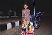 Young street seller working on the shores of Lake Hussain Sagar (Hyderabad) at night.