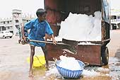 To preserve its catch of fish, each boat loads between 2000 and 3000 kilos of ice before it goes out to sea. The loading is often done by children. Port area of Mangalore, India.