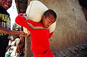 Addis Ababa, Ethiopia. Young house maid carrying a bag of grains weighing more than 30 kilos.