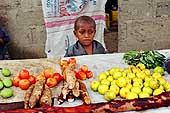 Zanzibar Island. Young children with his market stall on a road.