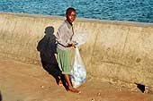Street child collecting trash at at the fish market in Dar Es Salaam.