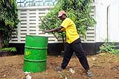 A young employee of the Dar Es Salaam municipality cleans the streets. Dar Es Salaam.