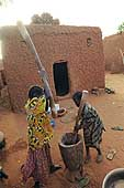 Young girls crushing millet. Village of Illela, (Tahoua area) Niger.