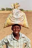 Child carrying a bag of millet. Nomad camp of Tajae (Tahoua area) Niger.