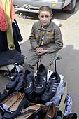 Young boy selling shoes in a marketplace in Chisinau, Moldova.