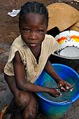Little girl doing the dishes in the street. Torokogou area, Bamako, Mali.