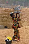 Young girl about to clean cookwares in Ségou harbour, Mali.