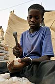 Young boy pruning stone blocs at Mopti harbour, Mali.
