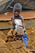 Young boy craming sand at Kalaban Koro sand harbour, Mali. 