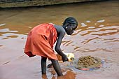 Young girl collecting sand at Kalaban Koro sand harbour, Mali. 