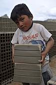 Young boy carrying bricks in a brickyard in La Paz (Alto), Bolivia.