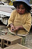 Young girl carrying bricks in a brickyard in La Paz (Alto), Bolivia.
