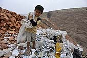 Young boy reprocessing plastic waste material in a dump. Lima, Peru.