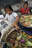 Children collecting food for animals in a dump. Lima, Peru.
