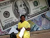 This photo is the result of a photographic competition organized by the International Labour Office New Delhi branch to promote decent work for domestic workers. Original caption by the author: Dollar dreams: The photo is of Vimlamma, who works as domestic help at homes in Bangalore to earn her living. When I requested for her photo, she chose to pose with the backdrop of currency notes. Indeed she has big dreams in her eyes!