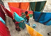 This photo is the result of a photographic competition organized by the International Labour Office New Delhi branch to promote decent work for domestic workers. Original caption by the author: Changing roles: Sonali, the domestic help at my home is seen in a very happy mood with my kid. As the clothes are hung out to dry in the sun, my son lends her his helping hand. Together they have fun!