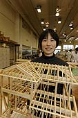 Female carpenter student presenting her wooden house model. Carpentry section. Kyoto Vocational Training School. Kyoto, Japan.
