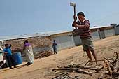 Sri Lanka. Boy tries to help to the reconstruction of his city cutting wood.