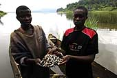 Former child soldiers who have benefited from the ILO's International Programme on the Elimination of Child Labour (IPEC). This programme aims at the reintegration of youth into civilian life. The pirogue and fishing nets have been given to them at the end of their training. Lake Kivu. Democratic Republic of the Congo.