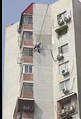 This worker is hanging dangerously by a rope while painting the building's walls. Construction site. Beijing. China.