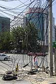 Electrical wires hang dangerously in the street. Beijing. China.