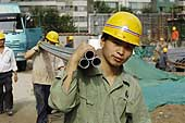 Men carrying metal pipes at a construction site employing internal migrant workers from the countryside. Beijing. China.