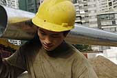 Man carrying metal pipes at a construction site employing internal migrant workers from the countryside. Beijing. China.
