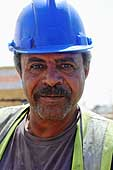 Portrait of a worker on a construction site. Orascom Construction Industries (Airport Tower). Orascom Construction Industries (OCI) is a leading construction contractor active in emerging markets. Based in Cairo, it employs more than 40,000 people in over 20 countries.