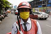 Traffic policeman protecting himself from surrounding pollution. Petchburi Road. Bangkok. Thailand.