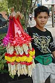 Child selling flower necklaces in Chong Nonsi. Business district. Bangkok.