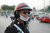 Policeman protecting himself from surrounding pollution. Petchburi Road. Bangkok. Thailand.