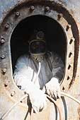 Worker on the 'Ameglia Star', Italian ship under renovation. Entrance of one of the hatches from which poisonous vapours emanate. Port of Genoa.