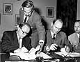 A. S. Tchistayakov, permanent representative of the USSR to the European Office of the United Nations, deposits instruments of ratification for 18 ILO Conventions on 10 August 1956. In attendance, ILO Director-General David A. Morse (with pen in mid-air).