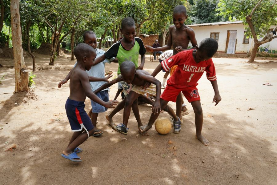 In Lilongwe, in a part of town known as AREA 23, a group of small children amuse themselves with an impromptu game of football on a clay playing field.