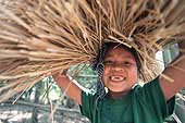 Child carrying rice straw, Cambodia